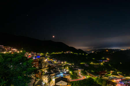 A night Landscape panorama view of ocean mountain and Jiufen village light. Stock Photo