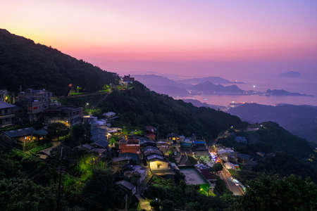 A Landscape panorama view of ocean and mountain with the beautiful sky. Taking photos during dusk at Jiufen Village.
