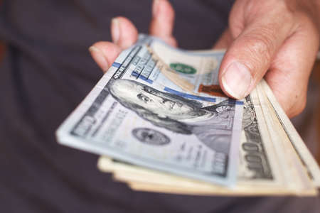 Hand holing American dollars banknotes background Фото со стока