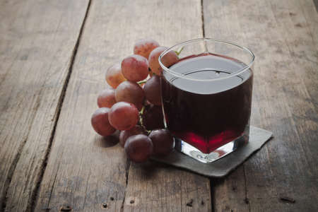 Grape juice on a wood background.
