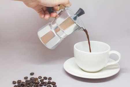 percolator: Moka pot and pouring coffee on a gray background.
