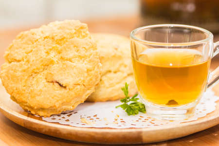 Place the scones on a plate, dessert and tea on wooden flooring.