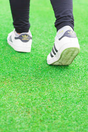 adidas: June 25, 2016 Adidas superstar shoes on white - illustrative editorial input jogging on the green grass in the park.