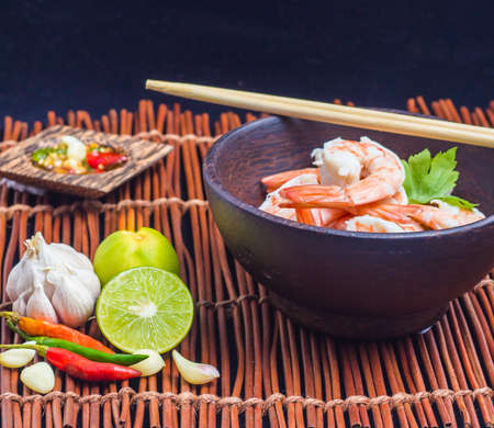 Boiled shrimp seafood sauce on wood background.