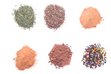 processed grains: the cocoa powder, ground coffee and dried tea leaves in a white container over white background.
