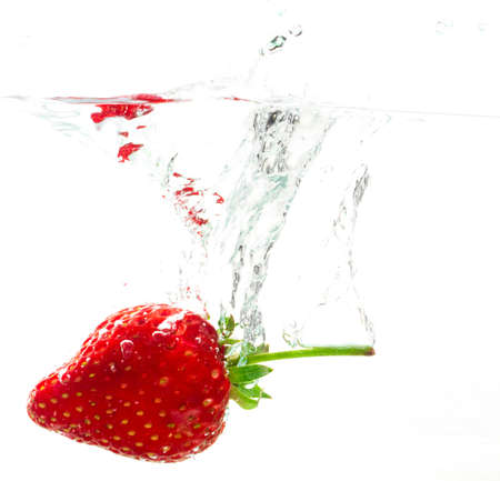 sinking: Throw the strawberries into water on white background