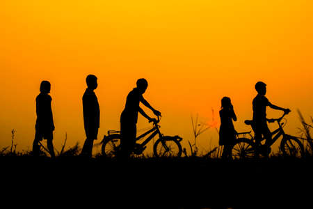 Boys and girls standing  behind a bike with sunset Silhouette.