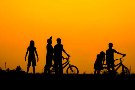 Boys and girls standing behind a bike with sunset Silhouette. Фото со стока