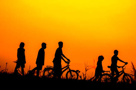 Boys and girls standing a bike with sunset Silhouette.