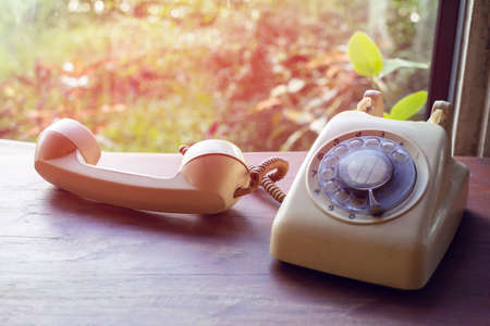 Old phone on a wooden table with a light  Sunset background. Imagens