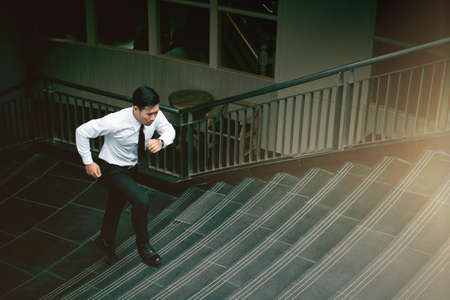 Motion blue Young Asian businessman running on  staircase go office hurry work time. Foto de archivo