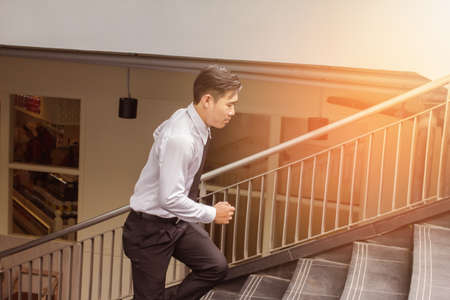 Young Asian Businessman running on stairs, rushing to office service. Outdoor, light sunset background