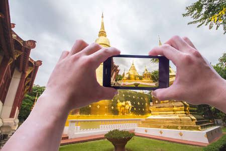Close up.man holding mobile phones take photos location and Golden Pagoda views, With blank copy space for your text message,Selective focus.Isolated white background Stock Photo