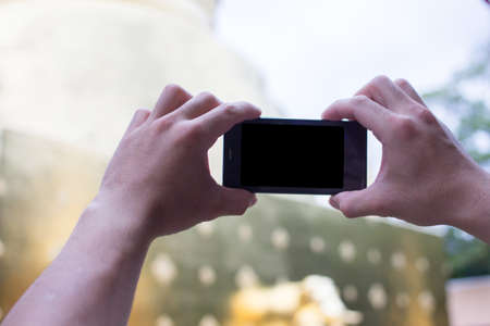 Close up Asian young man hands holding mobile phones take photos location and nature views, With blank copy space for your text message,Selective focus.Isolated white background Stock Photo