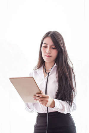 Woman doctor  standing looking using digital tablet on  white background.Selective Focus Stock Photo