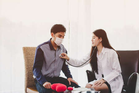 Asian female doctor examines heartbeat and talk about the health problems of the respiratory system of men.