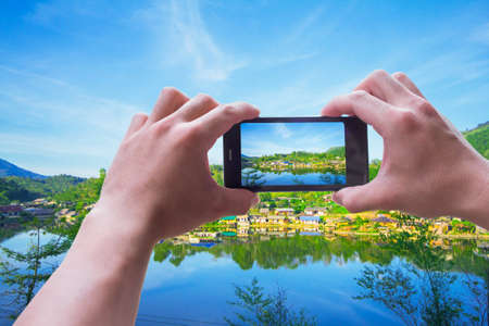 Close up.man holding mobile phones take photos location and Mountains, beautiful rivers , With blank copy space for your text message,Selective focus.Isolated white background