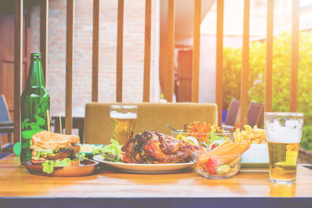 Beers, roasted turkey, vegetable salad, sandwiches and chips on wooden boards, concepts of holiday food.