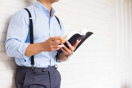 Half-length,Close up Man in blue shirt holding  black book of the Bible, Buddhist, Catholic, Christian, prayer,on wall background,Copy space for your text. Foto de archivo