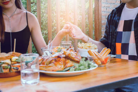 Two Asain women and one men hand thanking to God before eating food on table on (Thanksgiving Day)