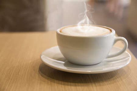 cup of hot coffee with foam and smoke on table in the morning. copyspace for your text