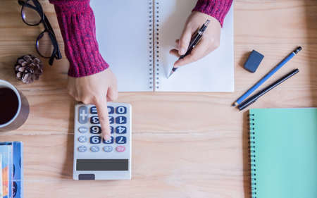 Top view. Hand woman doing finances and calculating on table  at home office.Concept finances and economy with book in morning Stock fotó