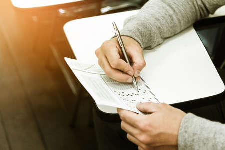 Student holding pencil writing on paper answer sheet.sitting on chair doing final exam attending in examination on classroom.
