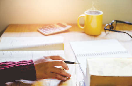 Close- up.School student holding pencil taking exams writing in classroom for education concept with sunset light background