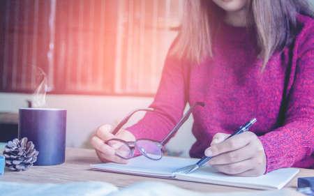 Woman right hand writing  on notebook at home area in morning with sun light  and vintage tone.
