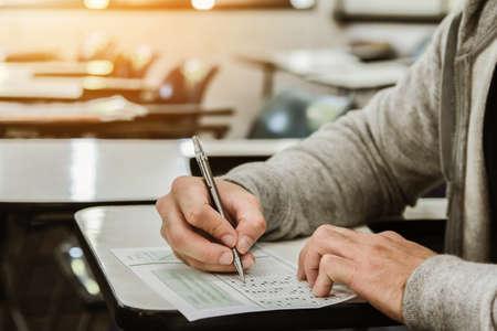 Étudiant, tenue, crayon, écriture, sur, feuille-réponse-papier