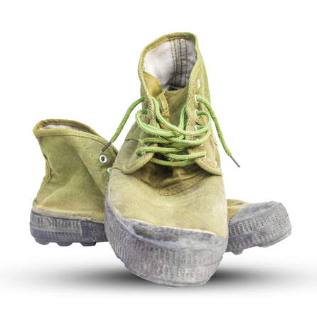 Green hiking shoes with dirty dust, white backdrop Stock Photo