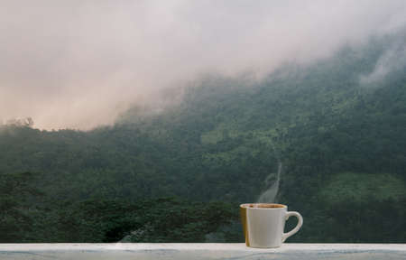 cup of hot coffee with and smoke on balcony in the morning. Fog and mountains, good atmosphere time,copyspace for your text.