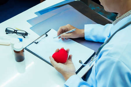 Doctor holding red heart and pen writing report Treatment Plan on desk with sunset light.Selective focus