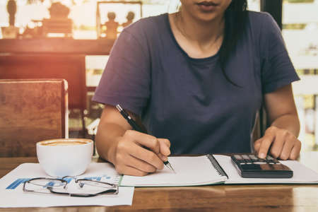 Asian young woman in blue shirt holding pen working ,Calculate tax lead to liquidation, With Sunset light vintage style.