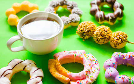 Top view, donut, chocolate, sweets and hot coffee or Americano. On a green backdrop