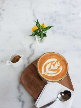 Hot coffee latte art  in cup on white marble background.