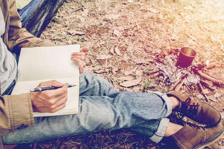 座っているアジアの若者は、テントの外で本を読んだり書いたりしています。森の中で一人でキャンプ。 写真素材