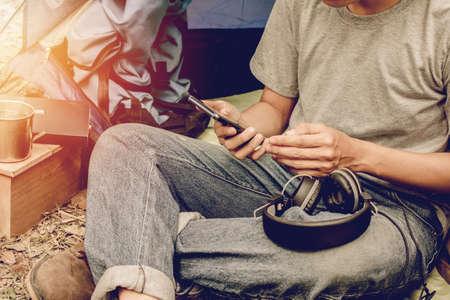 テントの外に座って携帯電話を使っているアジアの若者。森の中で一人でキャンプ。