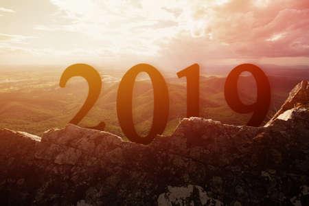 Sylwetka szczęśliwy na nowy rok 2019 na kamieniu z backgroung zachód słońca