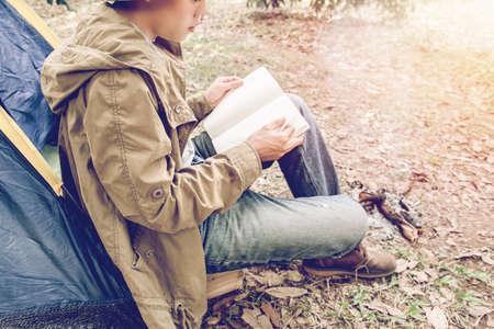 座っているアジアの若者はテントの外で本を読んでいます。森の中で一人でキャンプ。