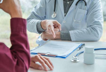 El médico señala el informe del remedio y la planificación del asesoramiento al paciente. Debe cuidarse cuando el dolor. Foto de archivo