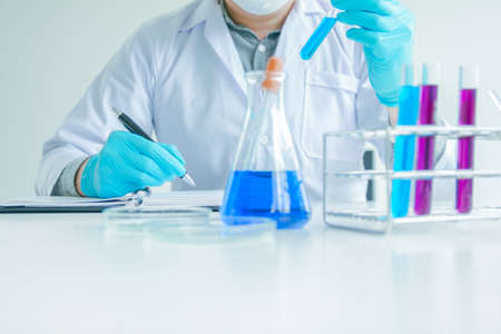 Medical science or male Compiling an Analysis Report in laboratory room research performs tests with blue liquid on test tube, Experimental Drug Treatment Chemicals