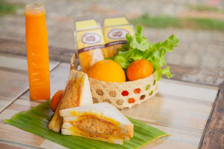 Sandwich ham and shredded pork is put on a banana leaf vegetables and orange juice on the table in the morning.