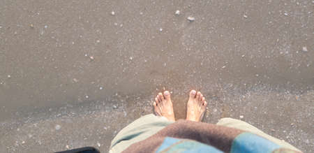 Close up of man in empty feet standing at the beach with a wave of foaming gentle beneath them.Top view 写真素材
