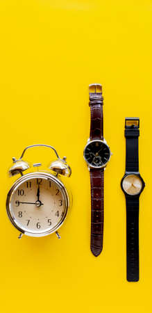 Top view. vintage clock and Watch. Minimal Style on yellow background use for wallpaper and screen