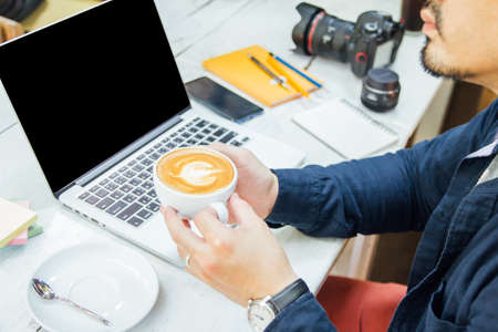 newsletter concept Hand of businessman holding cup of coffee and checking message box on digital laptop in the morning Reklamní fotografie