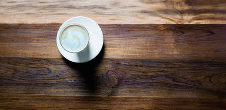 Top view,cup of hot coffee with foam and smoke on wooden table in the morning. copyspace for your text