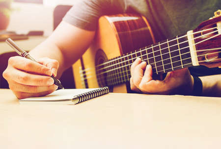 Romantic Guitar. Writing note musician or married man plays guitar on a black sofa at home.