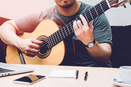 Romantic guitarist Composer or married man plays guitar sitting on black sofa at home. Stock Photo