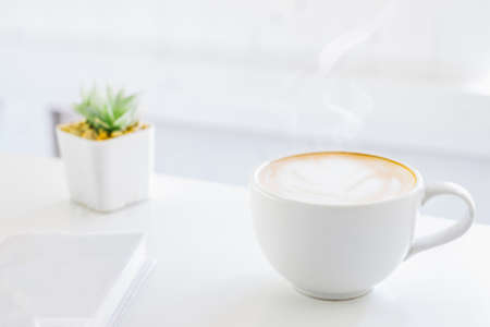 White cup of Latte art coffee as smoke with Flower Pot on wood table in the morning at home office,Clean white interior
